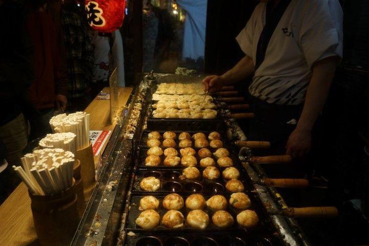 """Un tentempié ideal como aperitivo o para degustar entre horas: ¡el Takoyaki ! """"Tako"""" es pulpo, y """"yaki"""" es """"a la parrilla"""". El plato consiste en unas bolitas de agua, harina de trigo, y pulpo, que se cocinan en una plancha de hierro con huecos semicirculares (como podéis apreciar en la foto) y se sirven con salsa worcester, o salsa Perrins de toda la vida, recién hechos. Son típicos de la región de Kansai, y nosotros los probamos aquí, en Osaka."""