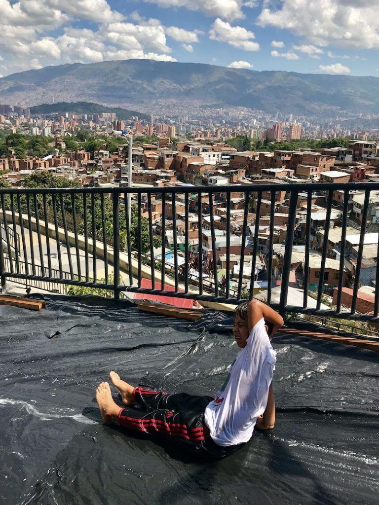 Un niño improvisa un tobogán en su casa, la Comuna 13, con una enorme bolsa de plástico, agua y jabón