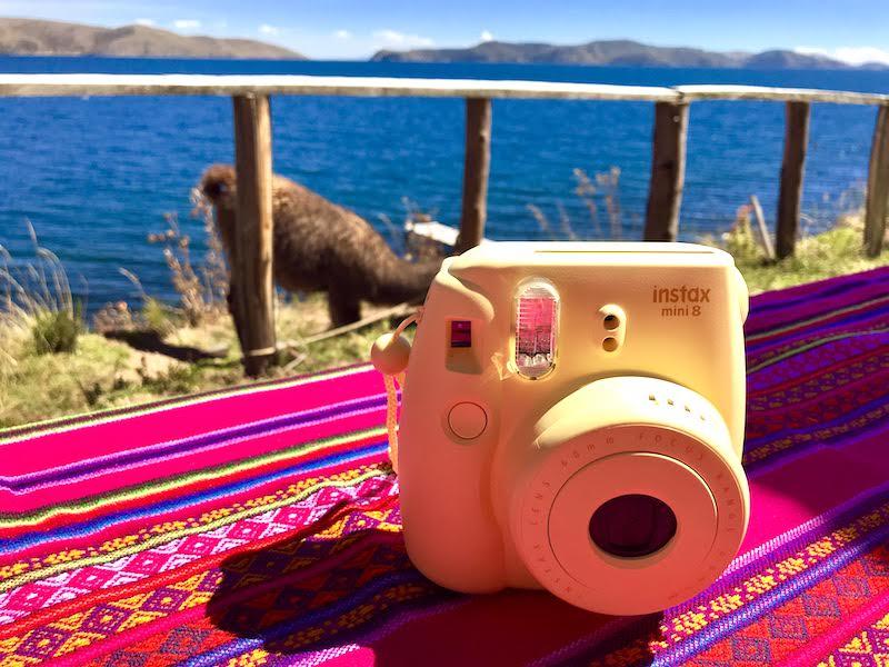 Nuestra cámara de fotos instantánea InstaxRandom con la llama Chico de fondo, en la isla de la Luna, Lago Titicaca, Bolivia