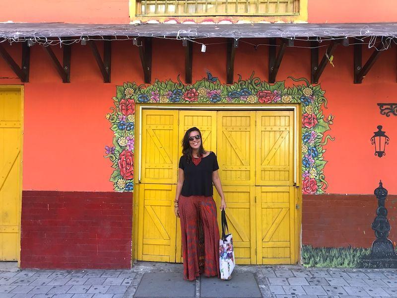 Inês frente a una colorida pared de El Poblado